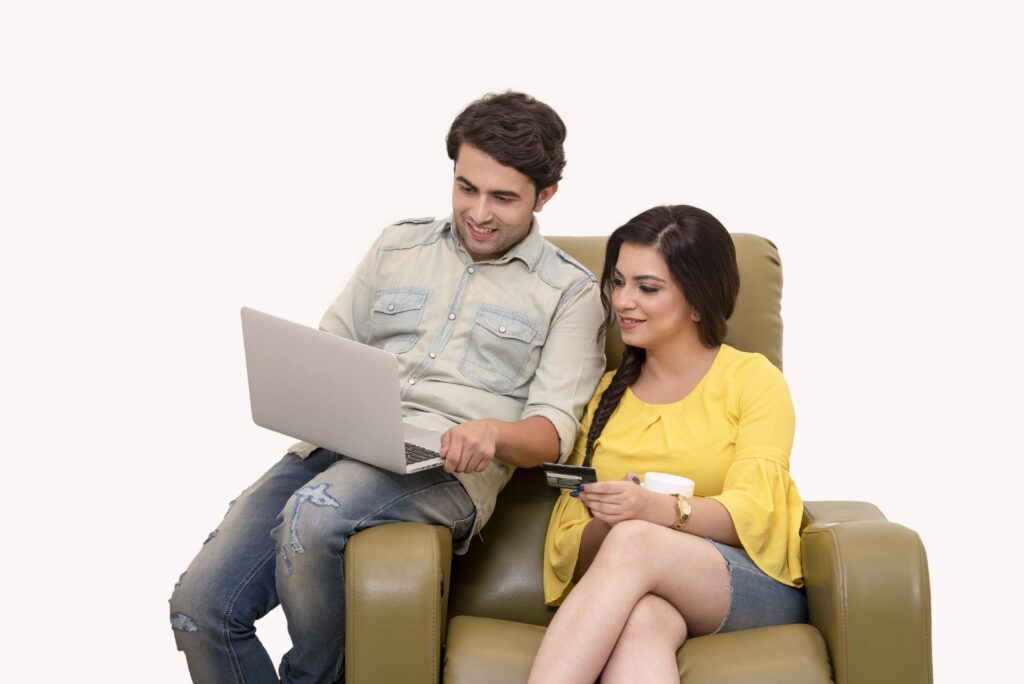 Two people sitting in a recline with one sitting in the armrests while holding a laptop