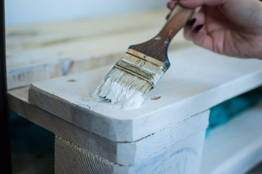 Hand brushing white paint over a table