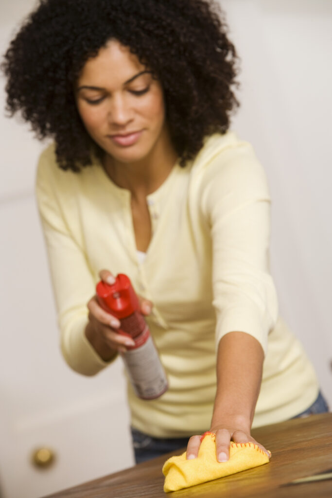 Woman cleaning wooden table with wood cleaning spray